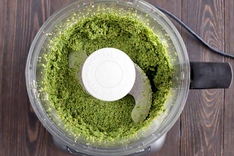 Overhead horizontal image of pesto in a food processor, on a brown wood surface.