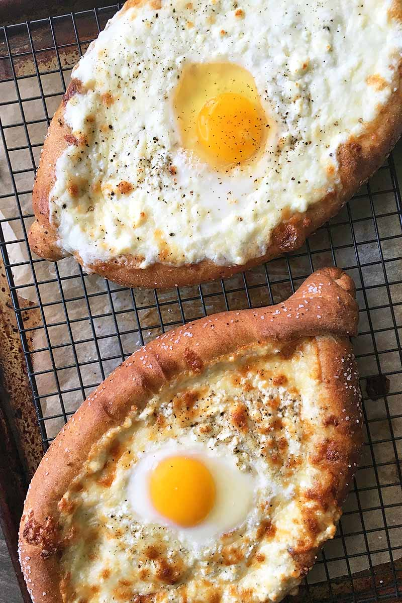 Vertical image of shaped shallow bread with melted cheese and eggs on a cooling rack.