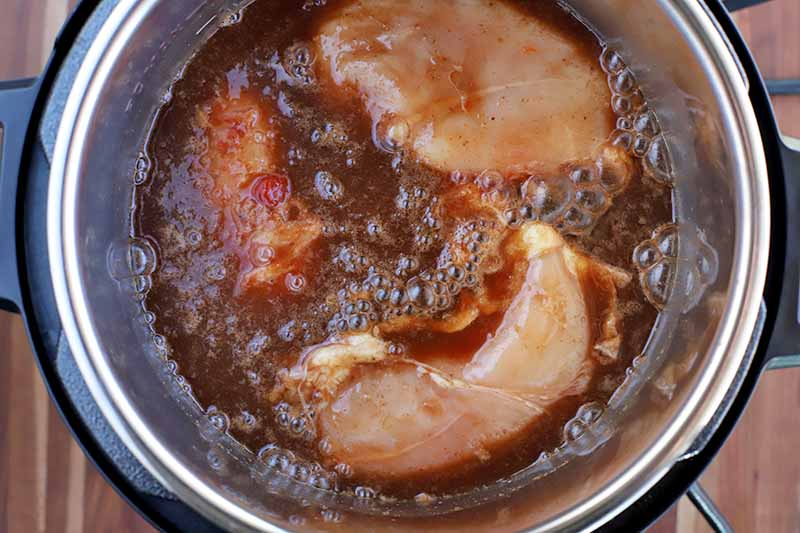 Raw chicken breasts in barbecue sauce and cola, in the metal insert of a slow cooker with black plastic handles, on a brown wood surface with vertical stripes.