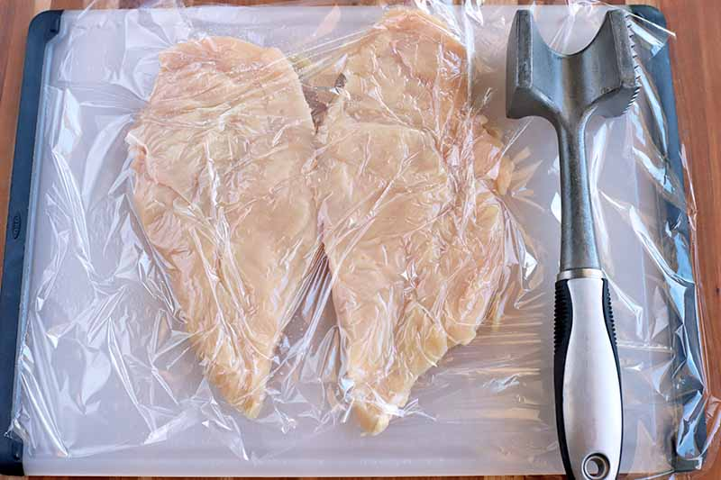 A butterflied chicken breast under plastic wrap, on a white and black plastic cutting board with a metal meat mallet to the right, on a wood surface.