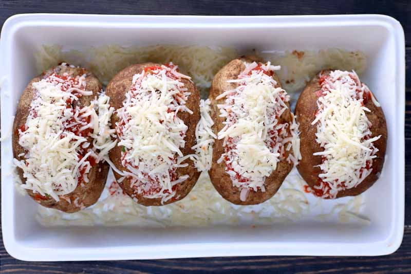 Overhead shot of four baked potatoes sliced open and stuffed with tomato sauce, meat, and vegetables, and topped with shredded mozzarella cheese, in a white ceramic baking dish, on a dark brown wood surface.