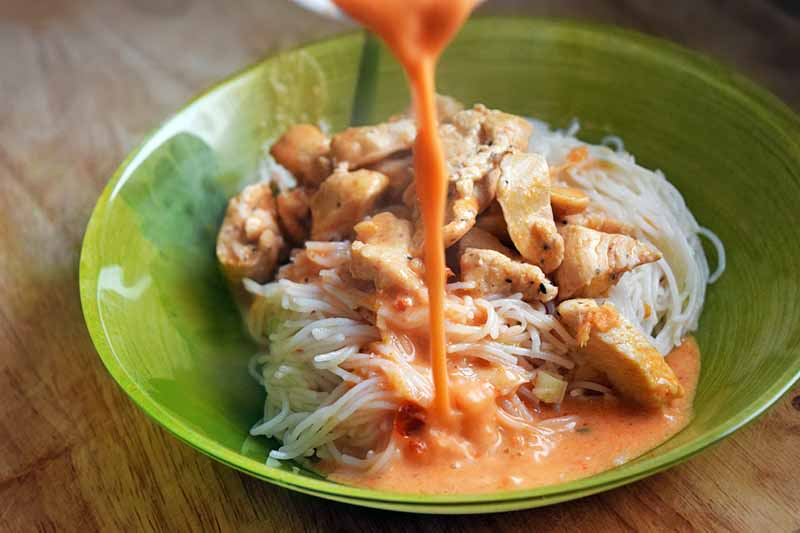 A red curry sauce is being poured into a green bowl of rice noodles and cooked chicken, on a wood surface.