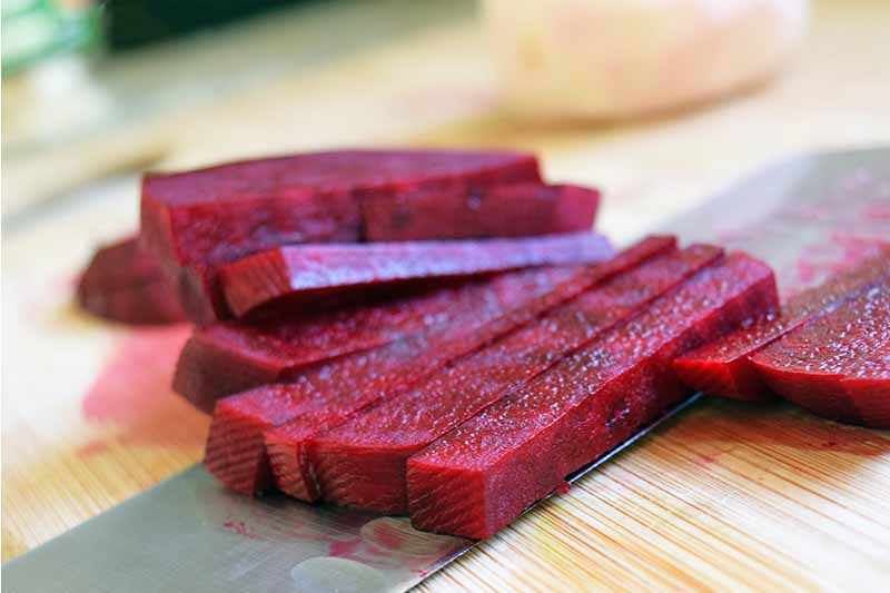 Closeup horizontal image of peeled beets sliced into thick matchsticks, with a knife on an unfinished wood cutting board.