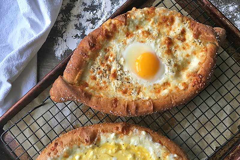 Horizontal image of baked bread with browned cheese and eggs next to a countertop with flour.