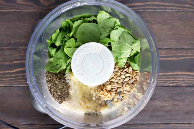 Overhead image of baby spinach leaves sunflower seeds, cheese, minced garlic, and seasonings in a food processor, on a brown wood surface.