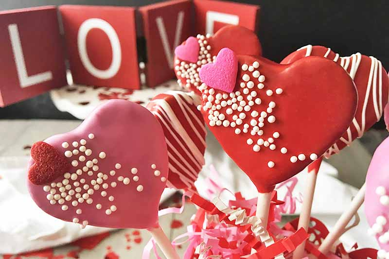 "Horizontal image of decorated cake pops with ""LOVE"" decor in the background."