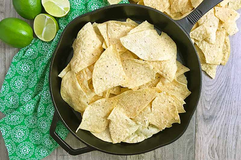 Horizontal image of a cast iron skillet with tortilla chips in it.