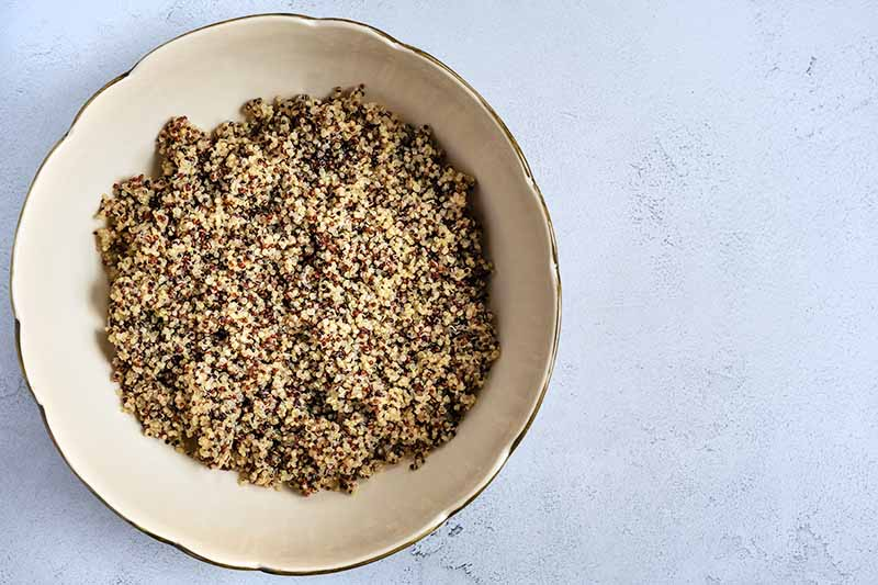 Overhead shot of a large beige ceramic bowl of cooked multicolored quinoa, on a white and gray speckled surface.