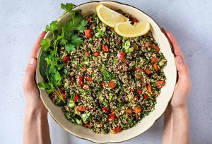 Overhead shot of two hands holding a large beige ceramic bowl of quinoa tabbouleh with tomatoes, green herbs, and yellow lemon wedges, on a white and gray speckled background.