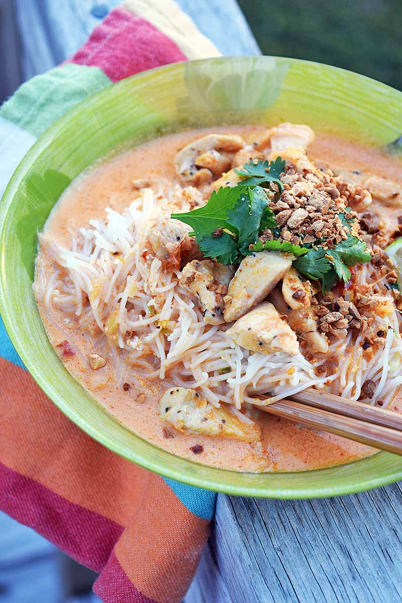 A pair of wooden chopsticks grasp rice noodles in a red curry broth with chicken and a garnish of cilantro and peanuts, on a multicolored cloth on a wood surface.