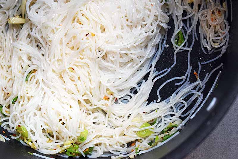 Closely cropped overhead closeup of cooked thin rice noodles with aromatics in a nonstick frying pan.