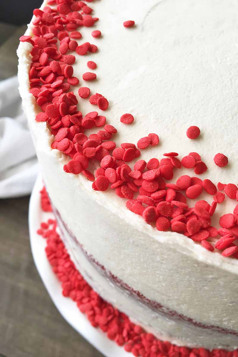 Vertical image of a decorated dessert with white icing and red sprinkles.