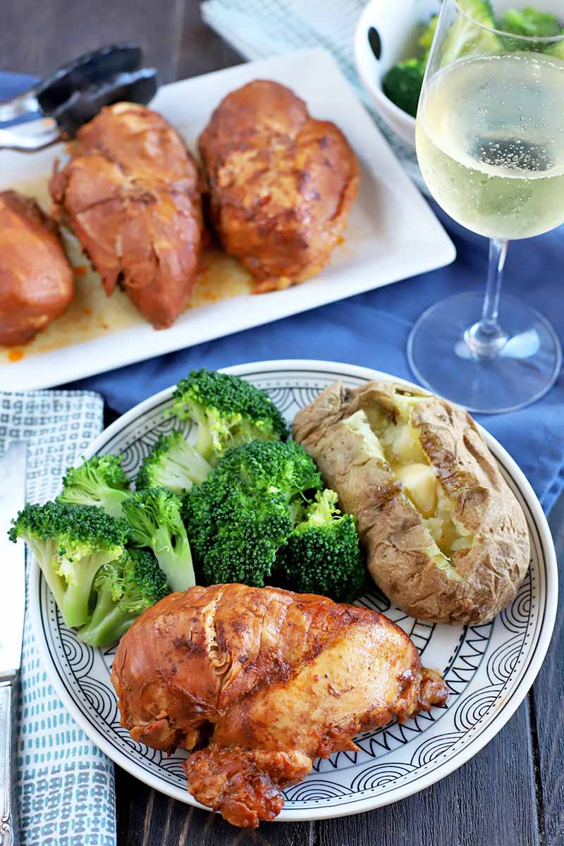 Vertical shot of a plate of broccoli with a barbecue cola chicken breast and a baked potato with butter, with a folded cloth napkin and silverware to the left and a glass of white wine to the right, with a serving platter of more of the meat with tongs in the background beside a bowl of steamed broccoli, on a blue cloth on top of a dark brown wood table.