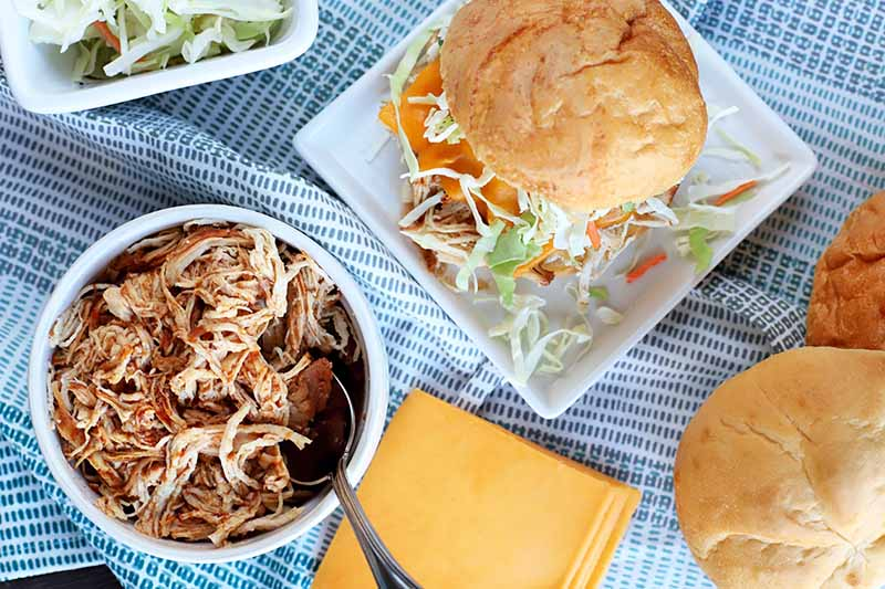 Overhead shot of a bowl of shredded barbecue chicken with a food, Kraft singles, sandwich rolls, and a square plate topped with a chicken sandwich, with a smaller dish of cabbage slaw at the top left corner, on a blue and white cloth.