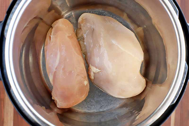 Overhead shot of two raw, boneless and skinless chicken breasts in the metal insert of a slow cooker, on a brown wood surface.
