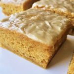 Horizontal image of orange dessert squares with a thin glaze on a white plate.