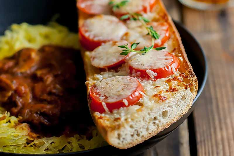 Horizontal close-up image of bread topped with cheese, tomato slices, and fresh herbs.
