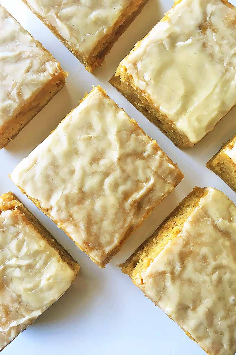 Vertical top-down image of dessert bars with a white glaze on a white plate.
