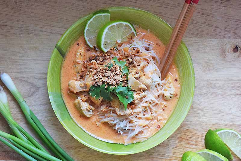 Overhead shot of a green bowl of red curry chicken with rice noodles and lime slices, with wooden chopstocks to the side, on an unfinished wood surface with scallions and green citrus wedges.