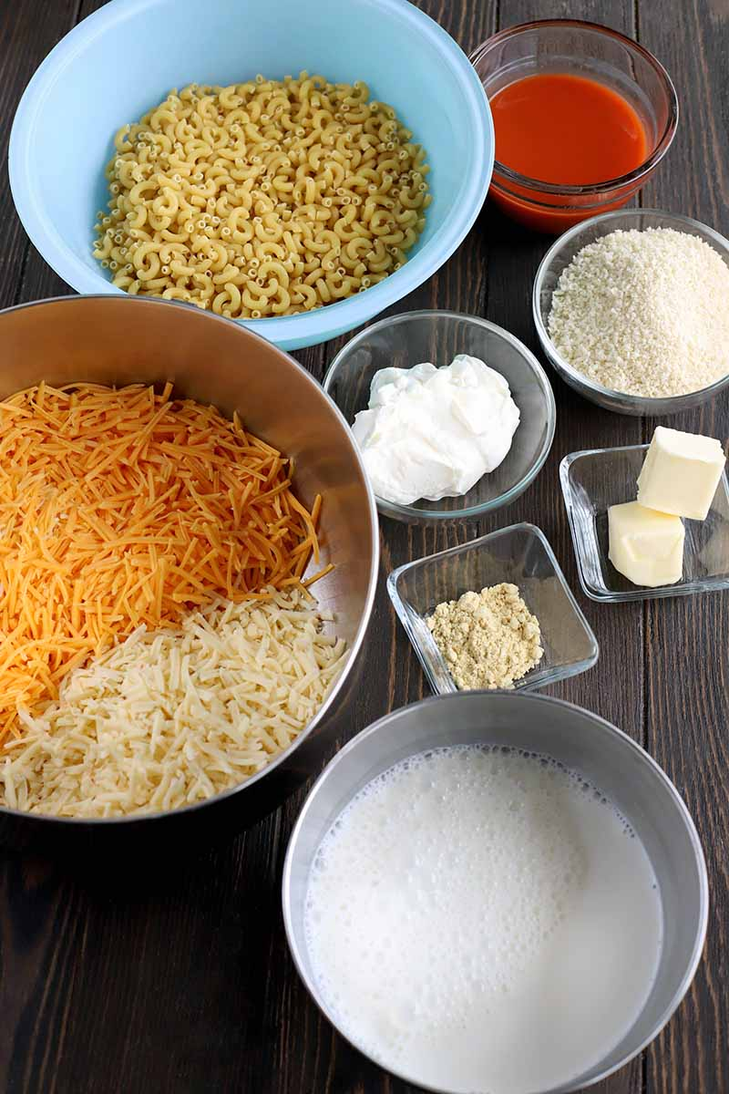 Overhead oblique shot of a light blue bowl of uncooked elbow macaroni, stainless steel bowls of shredded cheese and flour, and small square and round glass dishes of hot sauce, breadcrumbs, sour cream, butter, and powdered mustard, on a dark brown wood surface.