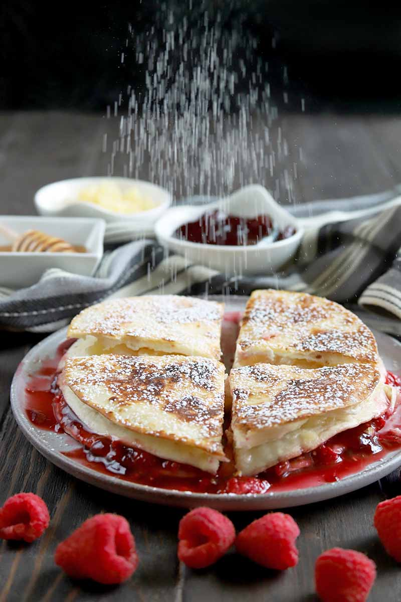 Vertical image of powdered sugar being sprinkled onto a dessert quesadilla on a white plate, with small white ceramic dishes of filling ingredients in soft focus in the background and scattered red raspberries in the foreground, on a brown wood surface with a black background.