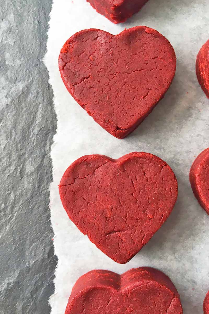 Vertical image of heart-shaped red dessert pieces on parchment paper.