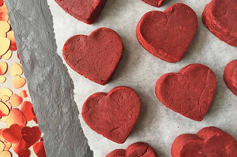 Horizontal top-down image of heart-shaped red dessert pieces on parchment paper.