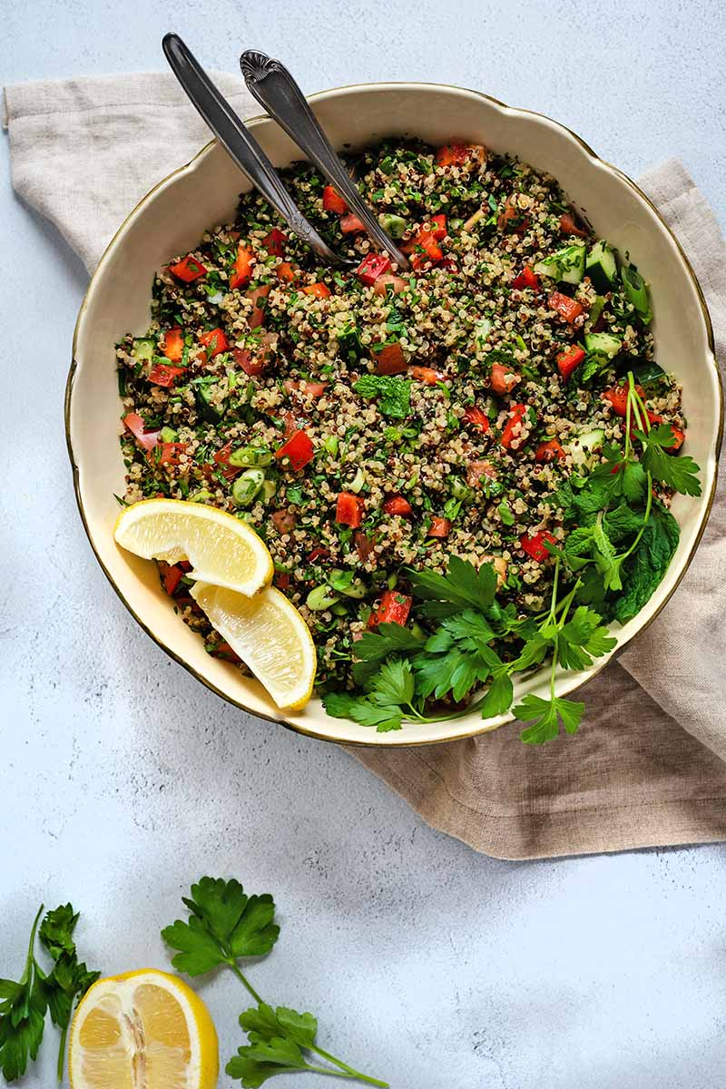 Overhead shot of a large, beige, ceramic bowl of quinoa tabbouleh with tomatoes, Italian flat-leaf parsley, and lemon wedges, with two metal serving utensils, on a folded beige cloth on a speckled white and gray surface, with a sprig of fresh herbs and yellow citrus.