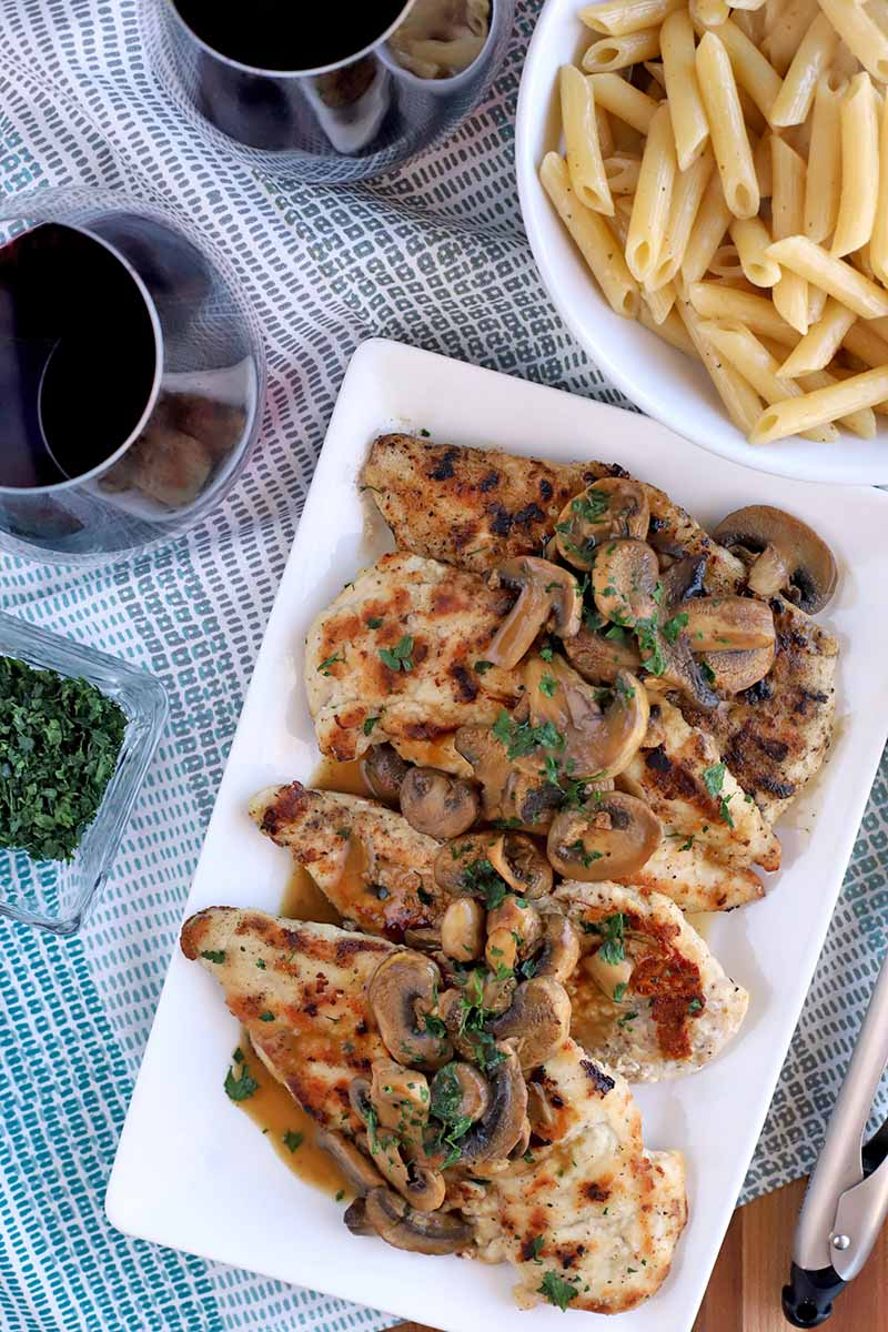 Overhead shot of a white ceramic rectangular serving platter of chicken and mushrooms with parsley garnish and brown sauce, next to a bowl of penne pasta and two glasses of red wine, and a small glass dish of chopped fresh green herbs, on a blue and white cloth.