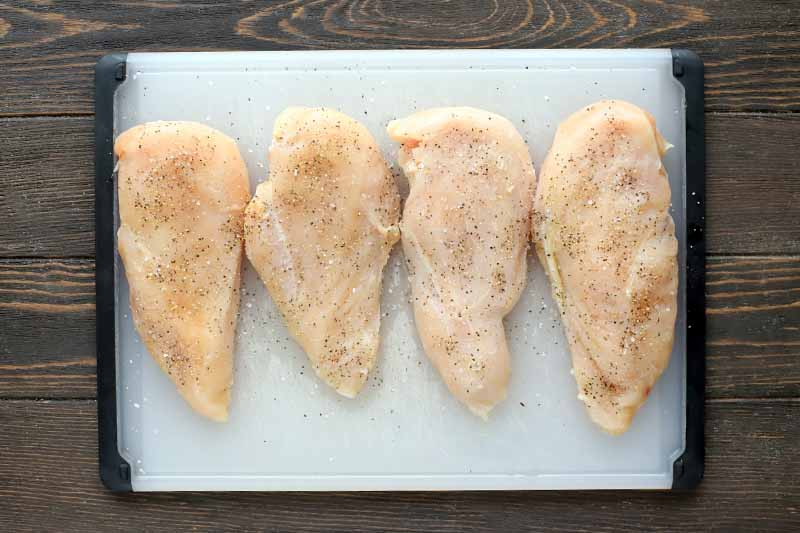Four skinless, boneless raw chicken breasts seasoned with salt and pepper are arranged in a row on a black and white plastic cutting board, on a brown wood surface.