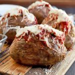 Four baked potatoes on a wooden board, filled with tomato sauce and melted cheese, with grated Parmesan sprinkled on top and in a small, square glass bowl to the left, with a stack of blue and white plate in the background, on a dark brown wood surface.