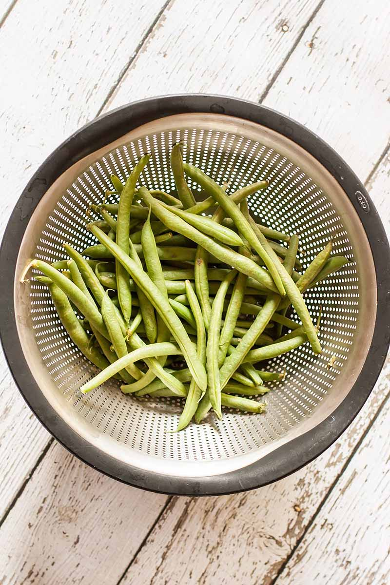 Vertical image of green beans in a strainer on a white wooden surface.