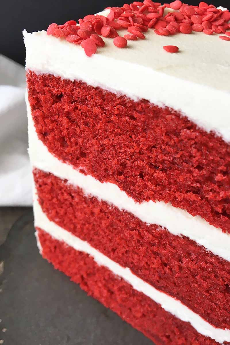 Vertical close-up image of a three-layered cake with white frosting in front of a white towel.