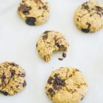 Top down view of a batch of chocolate chip cookies made with chickpea flour.