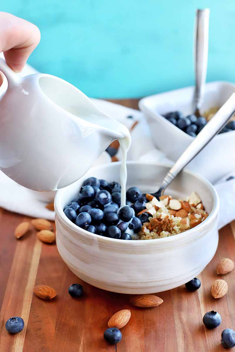 A hand outside the frame to the left pours milk from a white ceramic pitcher into a white bowl of quinoa, chopped almonds, and fresh blueberries, with a spoon, on a brown wood surface with scattered nuts and berries, and another square bowl with a spoon in the background, on a white cloth, against a robin's eye blue backdrop.