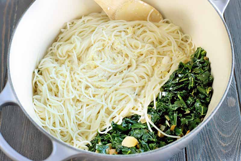Cooked pasta and kale about to be mixed together with a wooden spoon, in a large two-handled cream colored and dark blue cooking pot, on a dark brown wood surface.