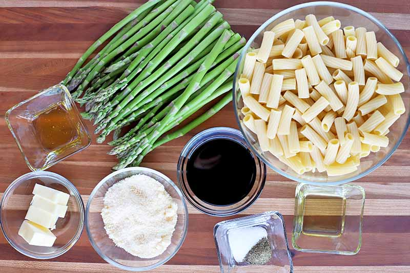 Overhead shot of a pile of thin green asparagus and round and square bowls of various sized filled with pasta, vinegar, olive oil, salt and pepper, grated cheese, butter, and honey,on a brown wood surface with horizontal stripes.