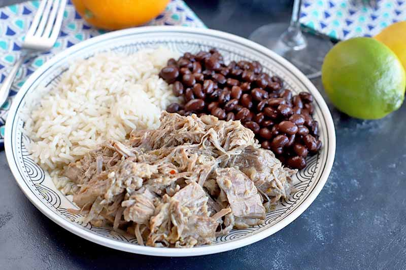 Horizontal image of a plate of pork, rice and beans next to whole citrus.