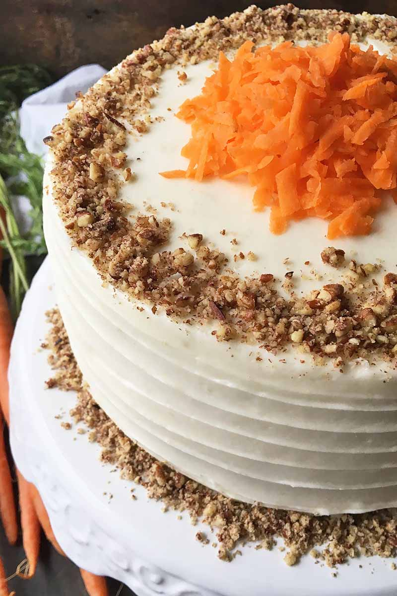 Vertical image of a whole decorated cake garnished with nuts and orange shreds on a white stand.