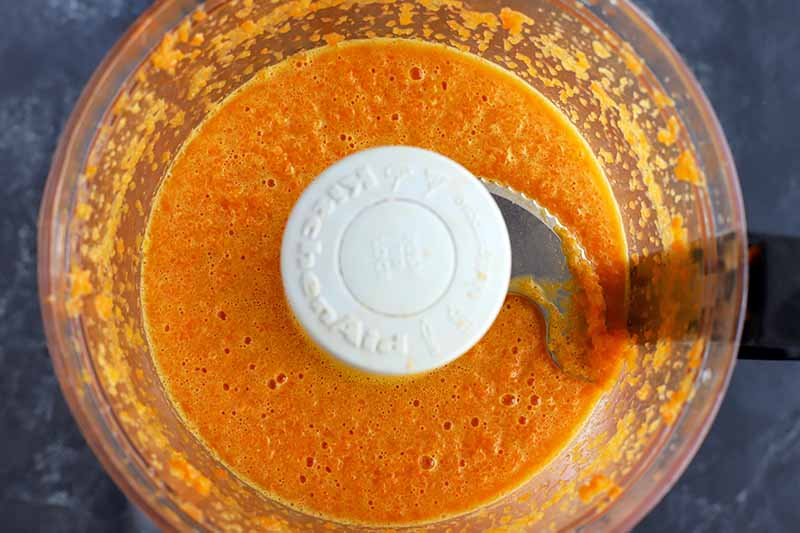 Overhead closely cropped horizontal shot of orange carrot puree in a food processor, on a dark gray slate surface.