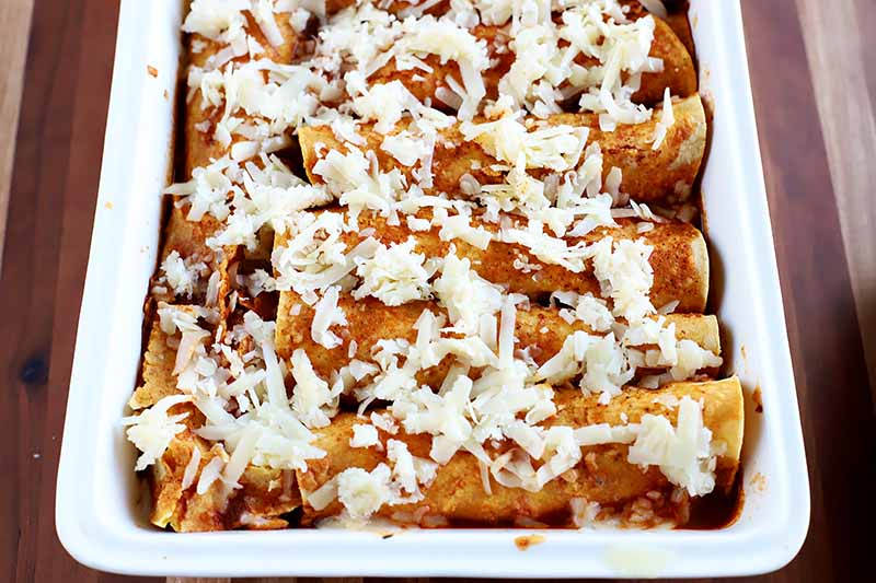 Horizontal image of white shredded cheese on top of tortilla shells covered in red sauce.