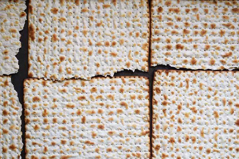 Overhead closeup of matzo crackers arranged so they are touching in two rows of three, on a metal baking sheet.
