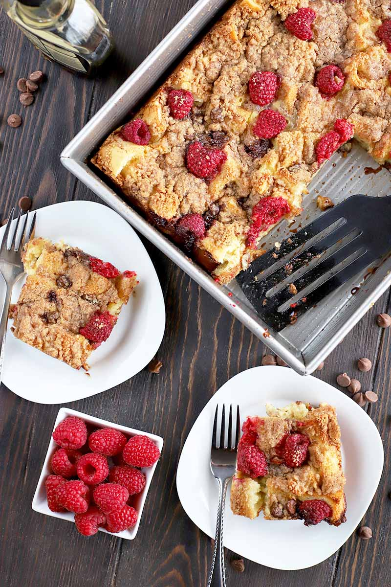 Overhead vertical shot of two white plates and a metal baking pan of French toast casserole, with a small square dish of fresh raspberries, forks, a plastic serving spatula, a glass bottle of maple syrup, and scattered chocolate chips, on a dark brown wood surface.