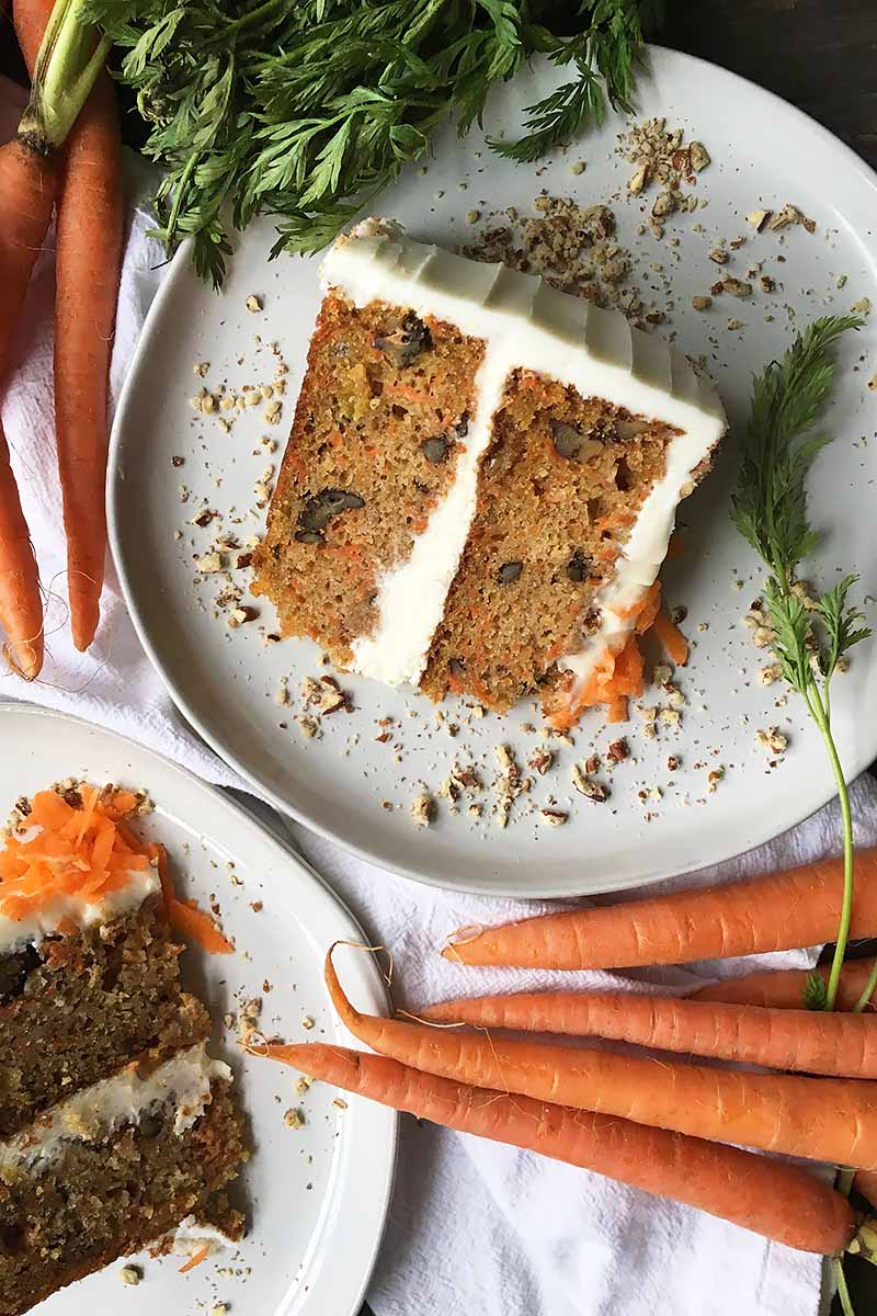 Vertical top-down image of two plates with slices of carrot cake next to fresh vegetables.