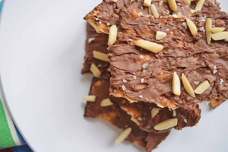 Horizontal closely cropped overhead shot of a stack of homemade chocolate almond toffee crunchies on a white plate with a green and white striped cloth beneath it.