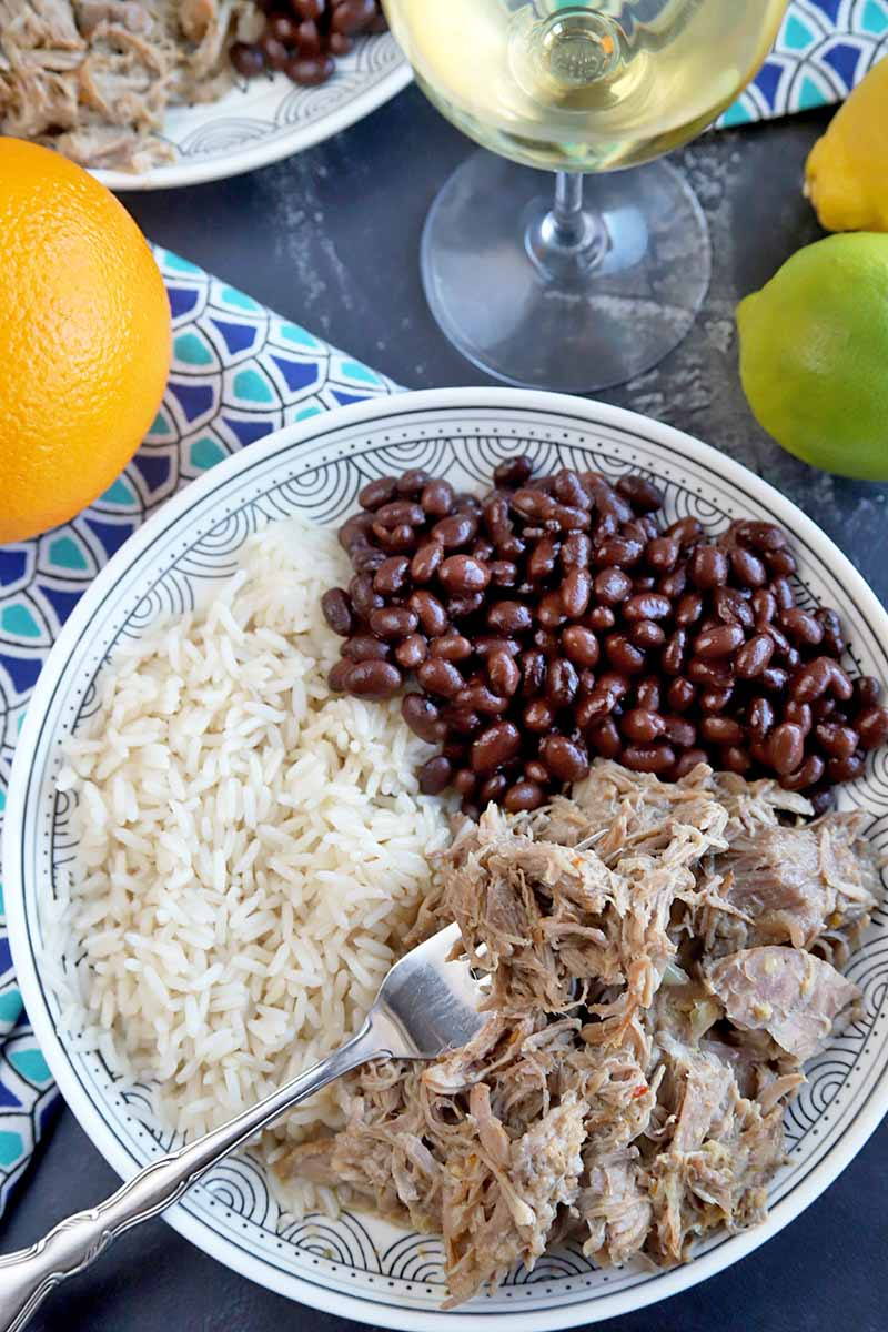 Vertical top-down image of a plate of meat, beans, and rice with a fork, next to a colorful napkin and citrus fruits.