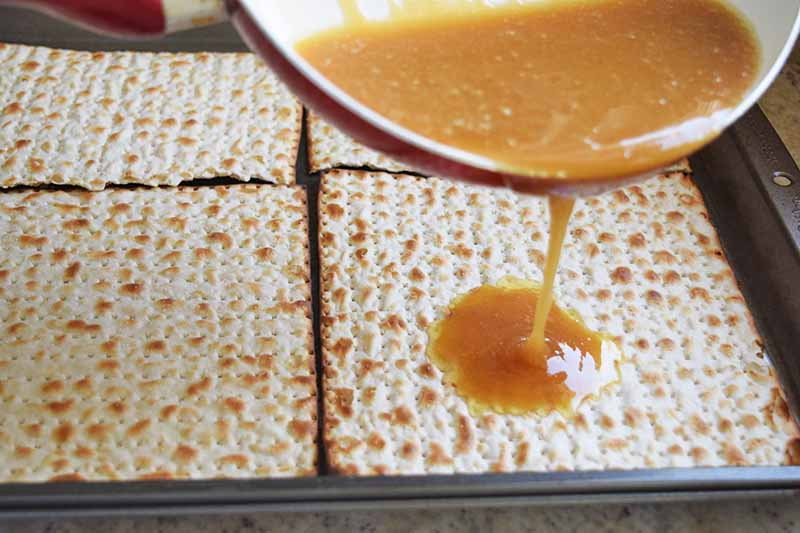 Loose caramel is being poured from a red and white frying pan onto matzo crackers arranged in two rows in a rimmed metal baking pan.
