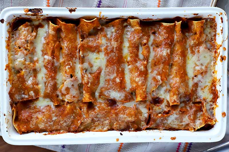 Horizontal image of a casserole dish full of wrapped tortilla shells covered in red sauce and melted cheese.