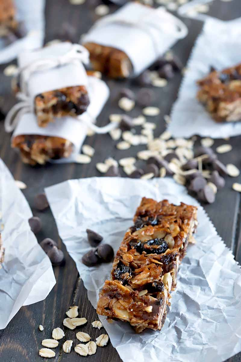 Vertical shot of granola bars, on pieces of parchment and wrapped in paper with string tied around htem, on a dark brown wood table with uncooked oats and dark chocolate chips strewn across it.