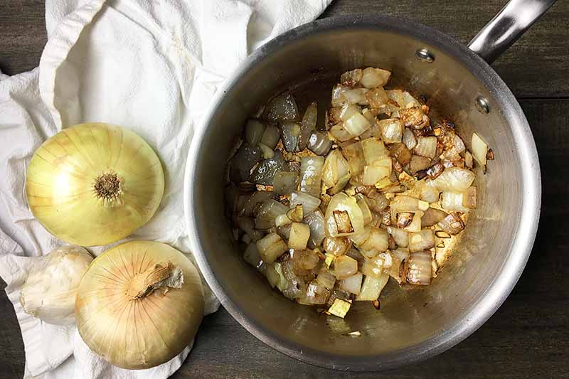 Horizontal image of a sauce pot with sauteed onions and garlic next to whole onions and garlic on a white towel.